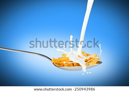 milk splashes on spoon with corn flakes - stock photo