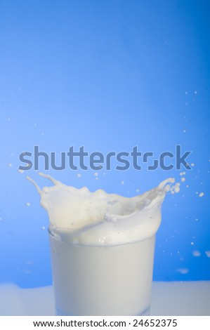 Milk splashing from a glass over blue background