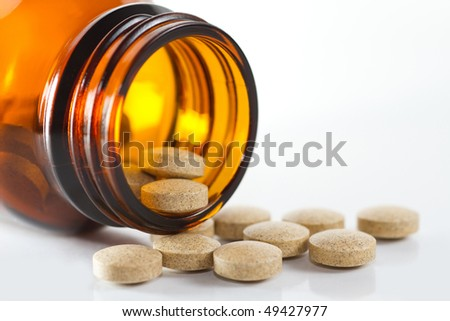 Milk thistle and dandelion herbal tablets with glass bottle on white background, selective focus. - stock photo