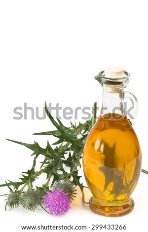 Milk thistle near glass bottle with oil on white background