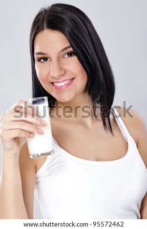 Milk - Woman drinking milk, happy and smiling beautiful young woman enjoying a glass milk - stock photo