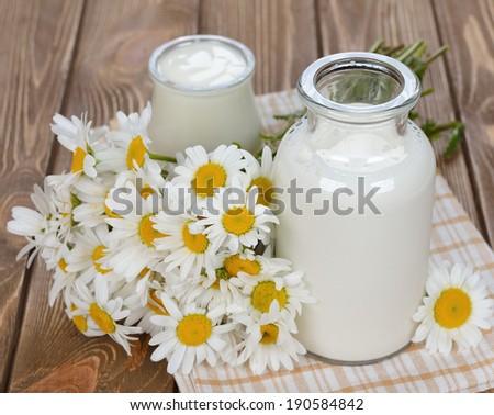 Milk, yogurt and chamomile on a brown background - stock photo