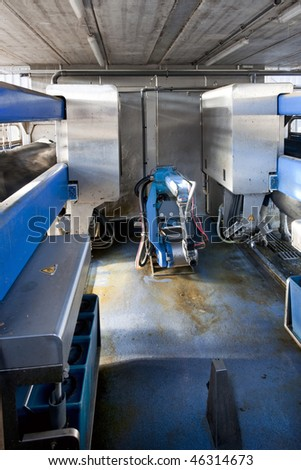 Milking robot interior, with two parallel bays to milk the cows in a dairy farm - stock photo