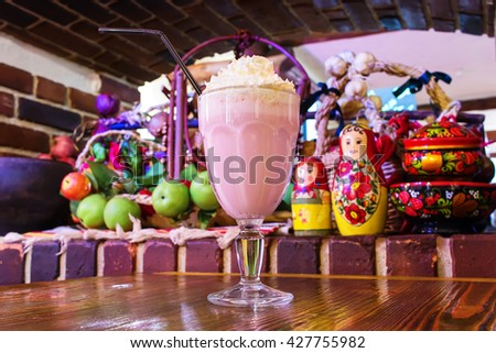 milkshake in a big beautiful glass with a straw on a wooden table - stock photo