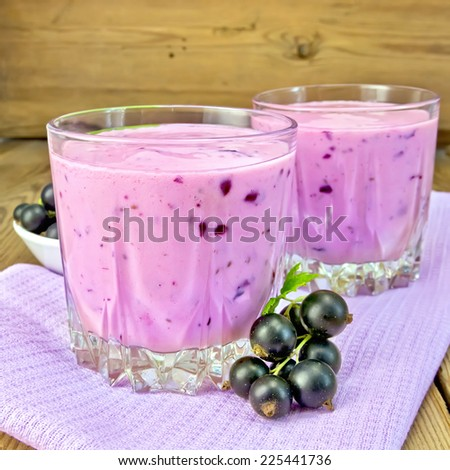 Milkshake with black currants in two low glass jars on a purple napkin, saucer with berries currants on a wooden board - stock photo