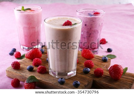 Milkshakes at cutting board with berries on light background - stock photo