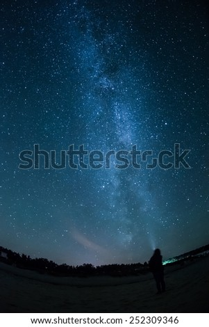 Milky Way above a beach and a human on the Baltic Sea of Germany, soft focus