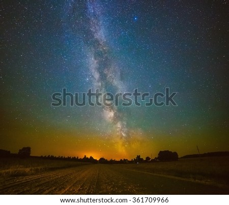 Milky Way galaxy above the road to the village - stock photo