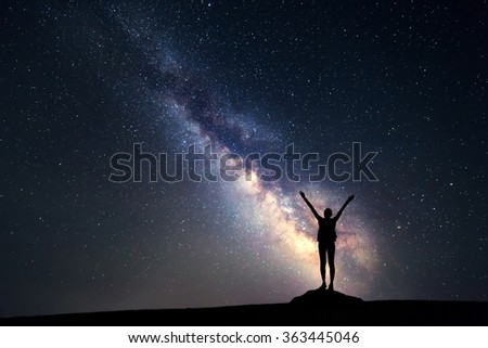 Milky Way. Night sky with stars and silhouette of a happy woman with backpack and raised up arms. Space background - stock photo