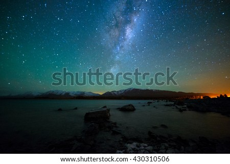 Milky Way Rising Above Lake Tekapo, New Zealand with Aurora Australis Or The Southern Light Lighting Up The Sky . Noise due to high ISO; soft focus / shallow DOF due to wide aperture used. - stock photo