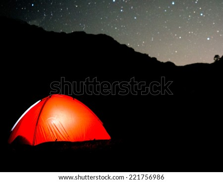 Milky way sky stars over mountain high tent camp - stock photo