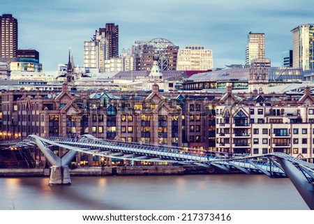 Millennium Bridge in London and skyscrapers in the background - stock photo