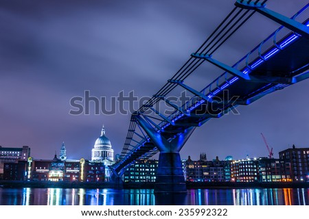 Millennium Bridge leads to Saint Paul's Cathedral in central London at night, cross processing - stock photo