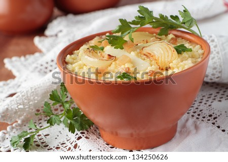 Millet porridge and fat and onions in a ceramic bowl