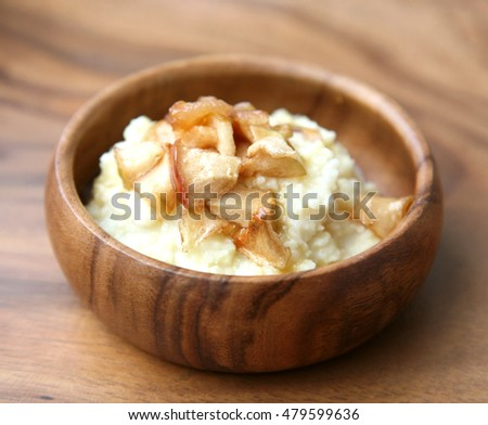 Millet porridge with baked apples on a wooden table