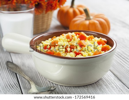 Millet porridge with pumpkin and milk in a pot on the table