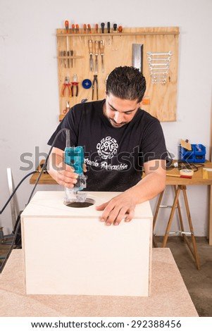 Milling machine being used to craft a cajon flamenco percussion instrument - stock photo