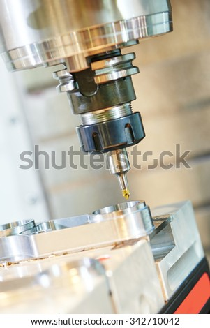 Milling machine tool with mill in chuck preparing to process metal detail at industrial manufacture factory - stock photo