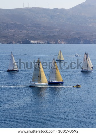 MILOS ISLAND, GREECE - JULY 21: Racing sailboats at the start of the 3rd Offshore Race: Milos � Cape Sounion of International Aegean sailing Rally, on July 21, 2012 in Milos island, Greece. - stock photo
