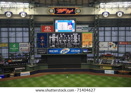 MILWAUKEE - APRIL 24: Brewers baseball player is dwarfed under the massive Miller Park Scoreboard during a game against the Chicago Cubs on April 24, 2010 in Milwaukee, Wisconsin. - stock photo