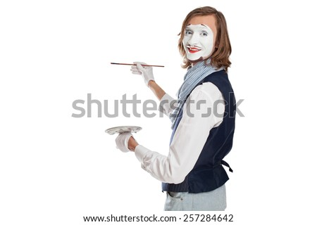 Mime Artist holding brush and easel and painting something - stock photo