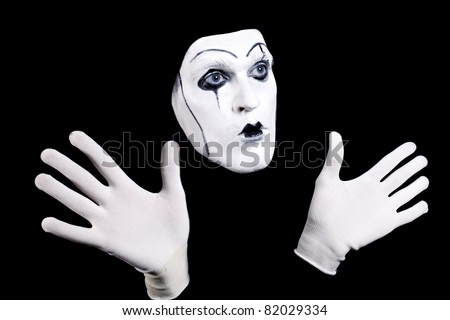 Mime face and hands in white gloves and a theatrical make-up isolated on black background - stock photo
