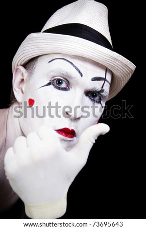 mime in striped gloves and white hat on black background - stock photo