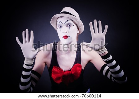 Mime with red bow in a white hat and striped gloves on black background - stock photo