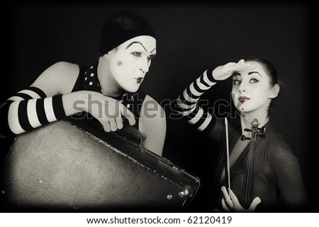 mimes woman and man with suitcase and violin - stock photo