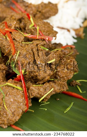 Minangkabau Beef Rendang on Banana Leaf w Steamed Rice in Background. Not sharpened - stock photo