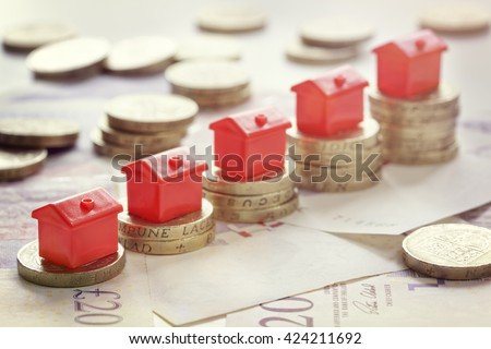 Minature houses resting on pound coin stacks concept for property ladder, mortgage and real estate investment - stock photo