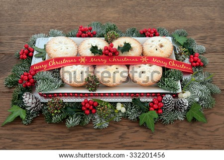 Mince pie cakes on a plate with red merry christmas ribbon, holly, mistletoe and winter greenery over old oak background. - stock photo