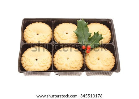 Mince pies in a carton with a sprig of holly isolated against white - stock photo