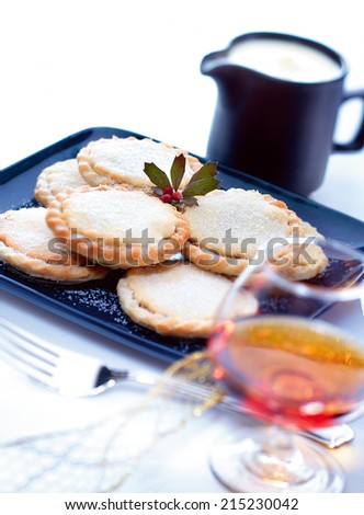 Mince pies on a plate with cream jug and brandy glass - stock photo