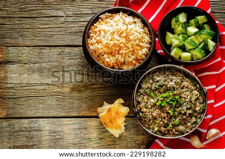 minced lamb, cooked with spinach on a dark wood background. tinting. selective focus on green onions - stock photo