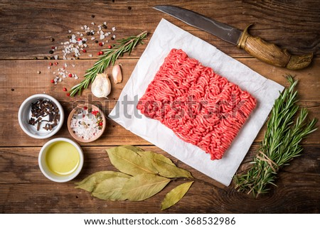 Minced meat on paper with seasoning and fresh rosemary on wooden background, top view - stock photo