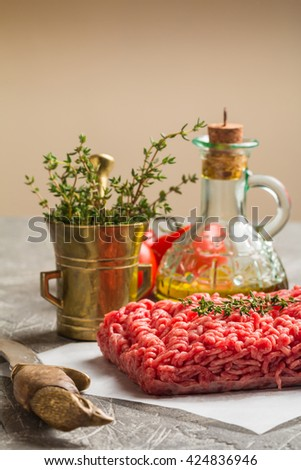 Minced meat with seasoning and fresh thyme - stock photo
