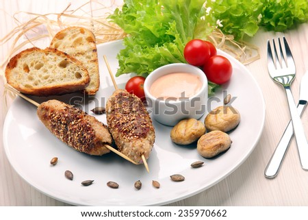 Minced meatballs baked as skewers with sesame seeds