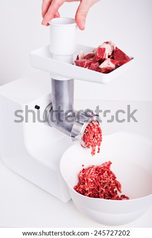Mincer machine with fresh chopped meat - stock photo