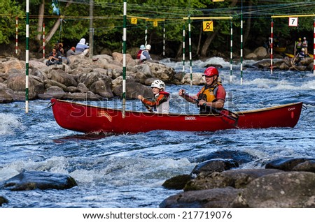 MINDEN, ONTARIO - SEPTEMBER 6, 2014: Father and son compete at 2014 Open Canoe Slalom Race at Gull River in Minden, Ontario, Canada.  - stock photo