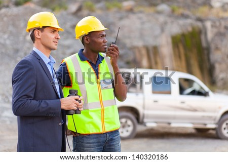 mine manager and worker visiting mining site - stock photo
