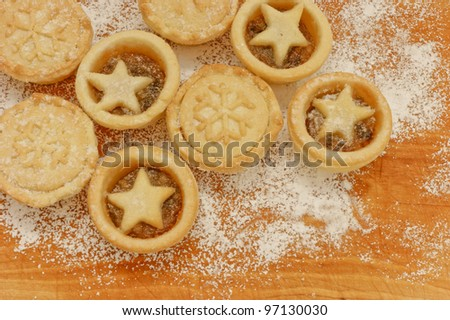 Mine pies selection. Festive home made mince pies on a scratched wooden table covered with icing sugar. Christmas baking concept. - stock photo