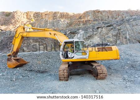 mine worker operating excavator on mining site - stock photo