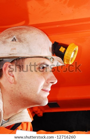 Miner operating a heavy duty machine in a mine shaft stock photo