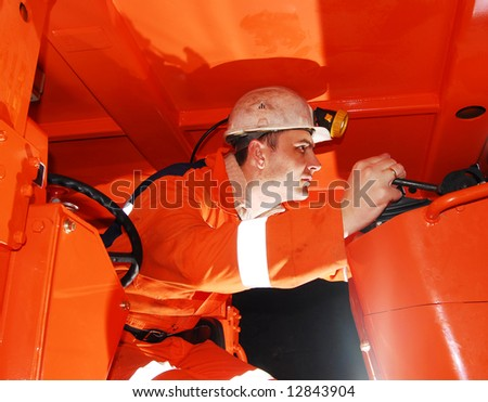 Miner operating heavy machinery in a mine shaft stock photo