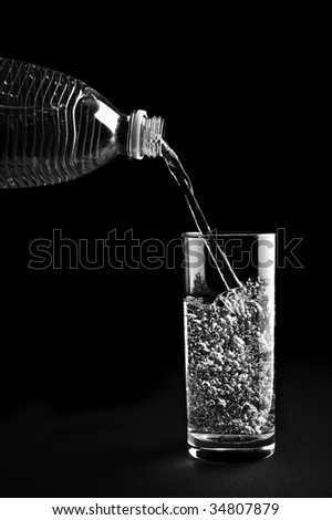 Mineral water being poured into a glass is isolated against a black background - stock photo