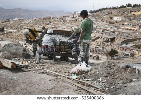Miners emptying mine cart at Cerro Rico silver mine in Potosi. October 8, 2012 - Potosi, Bolivia