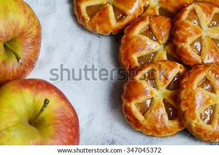 Mini apple pies with fresh apples and sugar background - stock photo