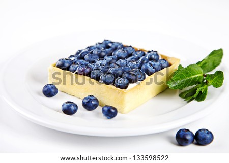 Mini cake with blueberries and mint on white background - stock photo
