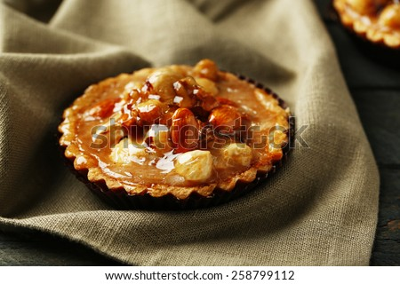 Mini cakes with nuts on napkin on wooden background - stock photo